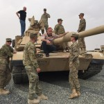 Dan Runte talks to the troops from on top of one of the tanks in the motorcade at Camp Beuhring.